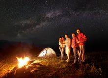 Turist- familj med dottern som har en vila i berg på natten under stjärnklar himmel med den mjölkaktiga vägen arkivbild