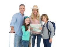Turist- familj som konsulterar översikten Arkivbilder