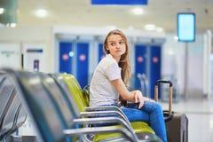Turist- flicka i internationell flygplats och att vänta på hennes flyg som ser förargat arkivbild