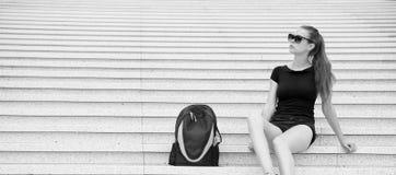 Turist- flicka koppla av på stenig trappa nära henne ryggsäcken Tagandeminut som ska kopplas av Stilfull svart dräkt för kvinnaso royaltyfri foto