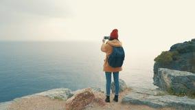 Turist- flicka med ett ryggsäckanseende på kanten av ett klippa- och skyttefoto lager videofilmer