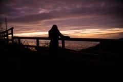 Turist- flicka på solnedgången ovanför en stad arkivbild