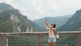 Turist- flicka som gör Selfie vid telefonen av bron Djurdjevic i Montenegro, lopplivsstil royaltyfri fotografi