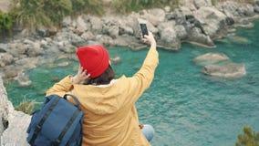 Turist- flicka som sitter på kanten av en klippa i lagun och skjuter selfie arkivfilmer