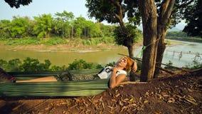 turist- flicka som sover på hängmattan, luangprabang, Laos Arkivbild