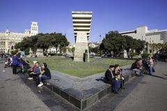 Turist- folk som sitter nära monumentet till Francesc Macia på Placaen de Catalunya, Barcelona, Spanien Arkivfoton