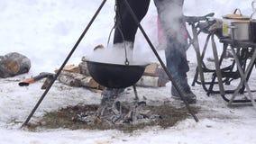 Turist- folkkock i krukan som hänger över lägereldbrand i vinter 4K stock video
