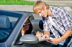 Turist- frågande kvinnligchaufför om riktning arkivbilder