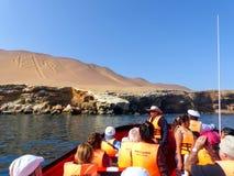 Turist- grupp i ett fartyg nära kandelaber av Anderna i Pisco lodisar Arkivbild