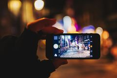 Turist- hand som rymmer den Apple iPhonesmartphonen som tar foto chris royaltyfria bilder