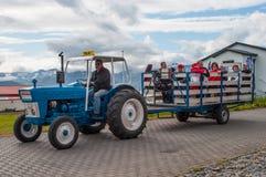 Turist- handbok som kör en traktor som drar en vagn med turister royaltyfri bild