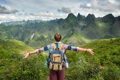 Turist i berg som tycker om på sikt av berg arkivfoton