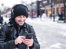 Turist i hörlurar som går ner gatan och använder hans smartphone Livlig aktiv livsstil Arkivbild