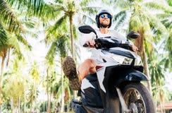 Turist i ritt f?r s?kerhetshj?lm en motoroler under palmtr?d fotografering för bildbyråer