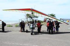 Turist i skugga av vingen av hängning-glidflygplanet på Airshow arkivbild