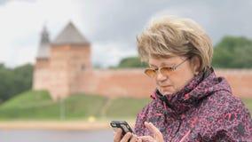 Turist- innehav för vuxen kvinna en smartphone utomhus lager videofilmer
