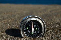 Turist- kompass i sanden Arkivfoton