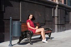 Turist- koppla av för ung drömlik kvinna efter staden som går, medan sitta på en träbänk i den nya luften, Royaltyfria Bilder