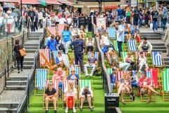 Turist- koppla av på deckchairs på fullsatta Camden Market i London royaltyfria foton