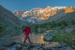 Turist- korsning bergflod fotografering för bildbyråer