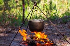 Turist- kruka som hänger över branden på en tripod Matlagning i caen royaltyfri foto