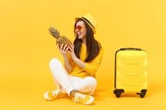 Turist- kvinna för glad handelsresande i sommarkläder, frukt för ananas för hatthåll som ny mogen isoleras på den gula apelsinen royaltyfri fotografi