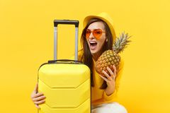 Turist- kvinna för gladlynt handelsresande i sommarkläder, frukt för ananas för hatthåll som ny mogen isoleras på den gula apelsi royaltyfria foton