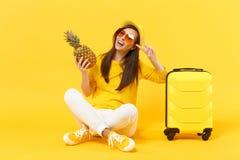 Turist- kvinna för handelsresande i frukt för ananas för håll för tecken för seger för visning för sommarkläderhatt som isoleras  royaltyfri foto