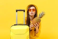 Turist- kvinna för handelsresande i hatt som blåser överföra luftkyssen för att rymma ny mogen ananasfrukt isolerad på den gula a royaltyfri bild