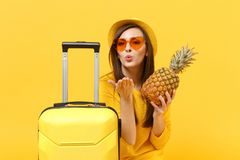 Turist- kvinna för handelsresande i hatt som blåser överföra luftkyssen för att rymma ny mogen ananasfrukt isolerad på den gula a royaltyfria foton
