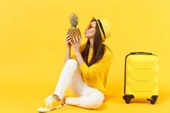 Turist- kvinna för handelsresande i hatt för tillfällig kläder för sommar som kysser ny mogen ananasfrukt som isoleras på den gul arkivbilder