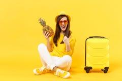 Turist- kvinna för handelsresande i sommarkläder, hattvisningtumme upp att rymma ananasfrukt isolerad på den gula apelsinen fotografering för bildbyråer