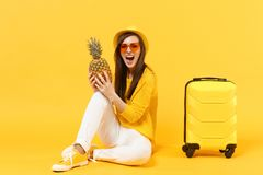 Turist- kvinna för handelsresande i tillfällig kläder för sommar, frukt för ananas för hatthåll som ny mogen isoleras på den gula arkivfoto