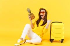 Turist- kvinna för upphetsad handelsresande i sommarkläder, frukt för ananas för hatthåll som ny mogen isoleras på den gula apels royaltyfri fotografi