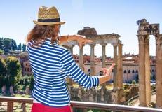 Turist- kvinna framme av Roman Forum som inramar med händer royaltyfria foton