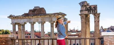 Turist- kvinna framme av Roman Forum som pekar på något fotografering för bildbyråer