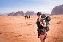 Turist- kvinna med vänner i en öken Den naturliga Jordanien parkerar Wadi Rum Fotvandrare på vägen Kvinnafotvandrare med ryggsäck arkivbilder