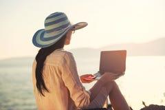 Turist- kvinna på ferier som direktanslutet tycker om med en bärbar dator på stranden arkivfoto