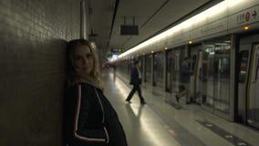Turist- kvinna på gångtunneltunnelbanan som ser till kameran Ung kvinna för stående på det väntande drevet för gångtunnelstation  lager videofilmer