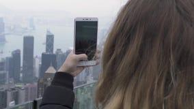 Turist- kvinna som fotograferar Hong Kong stadspanorama medan loppsemester Handelsresandekvinna som tar fotoet till mobiltelefone arkivfilmer