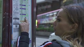 Turist- kvinna som ser schema- och ruttpassagerarebussar i station i modernasian stad för M Hålla ögonen på för handelsresandekvi arkivfilmer