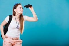 Turist- kvinna som ser till och med kikare på blått Royaltyfri Bild