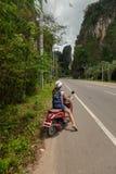 Turist- kvinnasammanträde på den klassiska sparkcykeln mot bakgrunden av bergen av det Krabi landskapet, Thailand royaltyfri fotografi