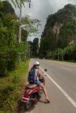 Turist- kvinnasammanträde på den klassiska sparkcykeln mot bakgrunden av bergen av det Krabi landskapet, Thailand royaltyfria bilder