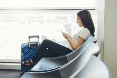 Turist- kvinnor som anv?nder telefonen p? v?ntande p? logi f?r internationell flygplats arkivbilder