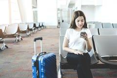 Turist- kvinnor som anv?nder telefonen p? v?ntande p? logi f?r internationell flygplats arkivfoto