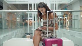 Turist- lycklig brunettflicka för nätt kvinna som direktanslutet shoppar med kreditkorten och minnestavlan i shoppinggalleria för stock video