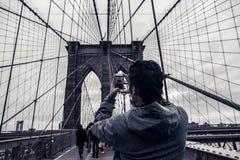 Turist- man Coceptual för filmiskt fotografi som tar bilden med mobiltelefonen på den Brooklyn bron, New York City USA arkivfoton