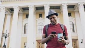 Turist- man för afrikansk amerikan som använder smartphoneonline-översikten för att finna rätta riktningar som står på gatan Arkivfoto