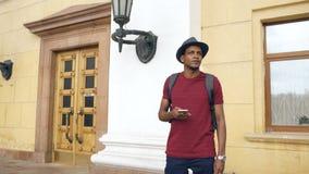 Turist- man för afrikansk amerikan som använder smartphoneonline-översikten för att finna rätta riktningar som står på gatan Arkivbilder
